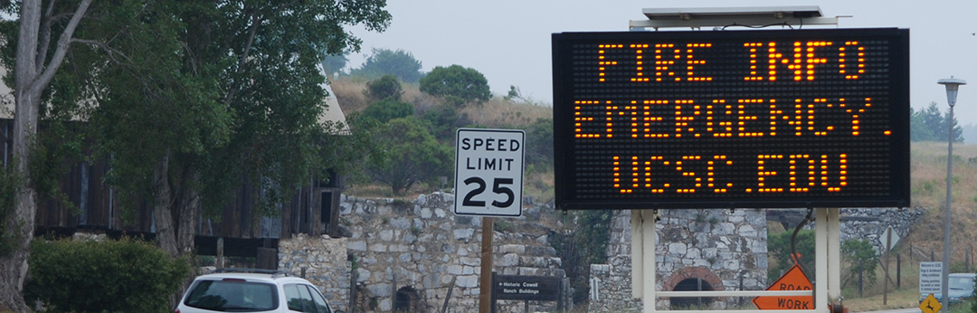 Photo of a roadsign with text reading Fire Info emergency.ucsc.edu
